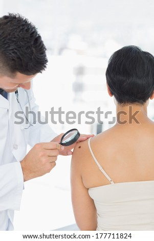 Dermatologist examining mole on woman with magnifying glass in clinic - stock photo