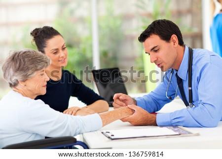 dermatologist inspecting senior patient skin in office - stock photo