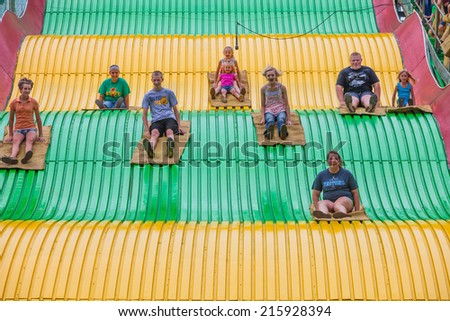 DES MOINES, IA /USA - AUGUST 10: Unidentified children on jumbo slide at the Iowa State Fair on August 10, 2014 in Des Moines, Iowa, USA. - stock photo