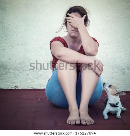Desaturated grunge image of a very sad adult woman crying (with a small dog besides her) - stock photo