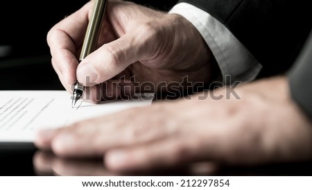 Desaturated image of the hands of a businessman signing a contract with a fountain pen. - stock photo