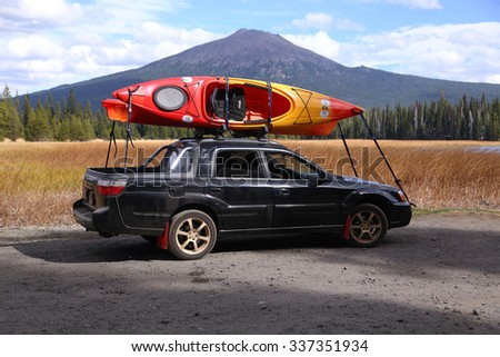 DESCHUTES COUNTY, OREGON - OCTOBER 10: Kayaks are loaded up and tied down on the roof rack of a Subaru Baja by Central Oregon's Hosmer Lake on October 10, 2015 with Mt. Bachelor in view. - stock photo