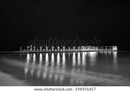 Description:  Night black and white photograph of the Waikiki Boat Pier. Title:  Waikiki boat landing.