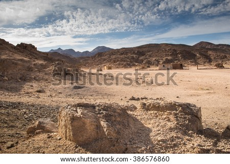 Desert and rocky mountains, Egypt Valley between the rocky mountains in egyptian desert. Place of bedouin village, building visible. Intense cloudy sky. - stock photo