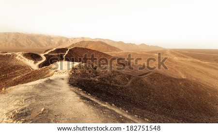 Desert dirty road near on white sky in Peru. - stock photo