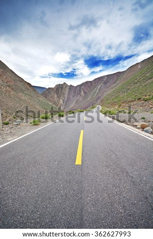 Desert highway shot into mountainous terrain under a blue sky