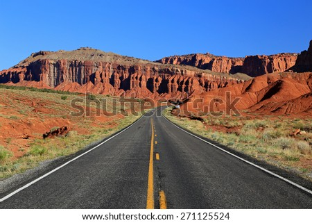 Desert highway with red rock cliffs, Utah, USA. - stock photo