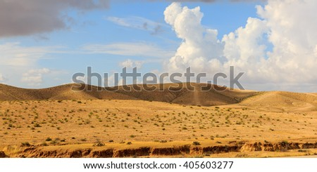 Desert hills under blue sky with clouds