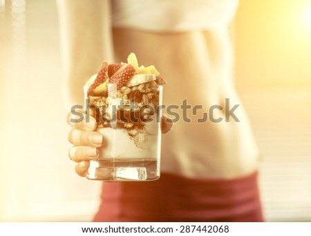 Desert in the hands of fitness female. - stock photo
