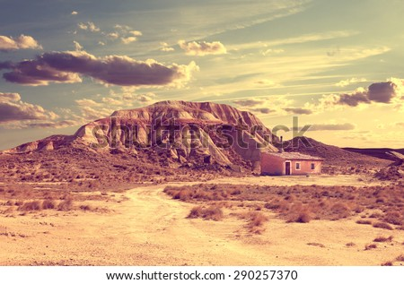 Desert landscape.House and road in sunset landscape - stock photo