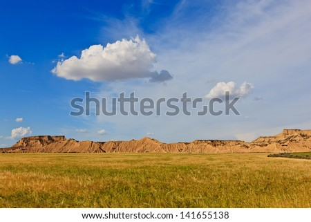 Desert landscape under the cloudy sky, Bardenas Reales, Navarra, Spain - stock photo