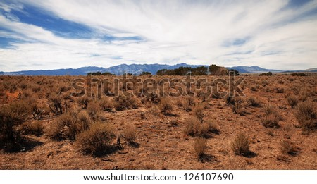 Desert landscape with hills in the distance. - stock photo