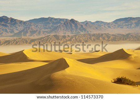Desert landscape with mountain and sand dunes in the foreground