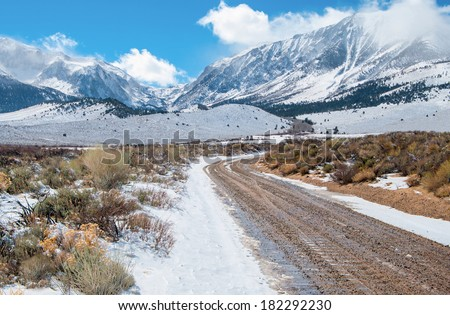 Desert Mountain Road in Winter:  A dirt road wet with melting snow leads across a desert plain toward the Sierra Nevada Mountains near Yosemite National Park.  - stock photo