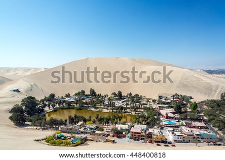 Desert oasis of Huacachina with a sand dune rising above it near Ica, Peru