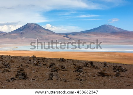 Desert plateau of the Altiplano. An ancient volcano and small lagoon in the background. Built of stones of a commemorative pyramid in the foreground. - Bolivia, South America