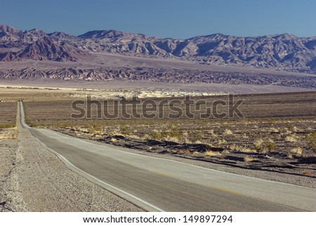 Desert road: toward Stovepipe Wells Village (SR 190) in Death Valley National Park, California. The Mesquite Flats Sand Dunes are visible in the background. Photo taken using a circular polarizer. - stock photo