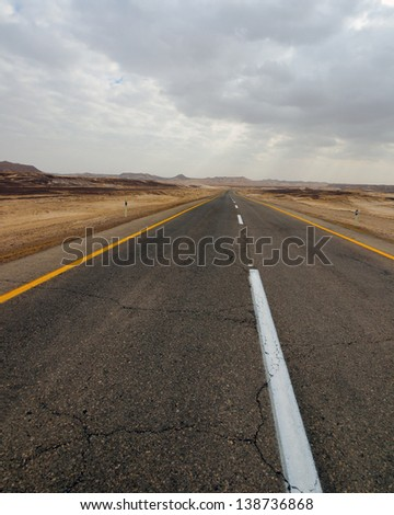 Desert road under dramatic cloudy sky. Arabah, Israel. - stock photo