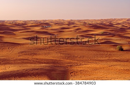Desert safari vehicles at sunset in the sand dunes outside Dubai City, United Arab Emirates