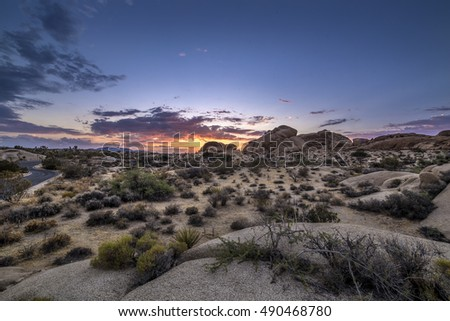 Desert scene turning into night during sunset also called golden hour when the sun has just set below the horizon of the landscape.