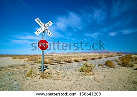 Desert stop sign and railroad crossing in California's Mojave Desert - stock photo