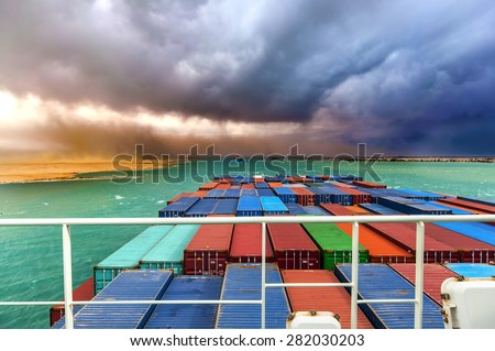 Desert Storm in SUEZ CANAL, Egypt. Container cargo ships going through the canal.