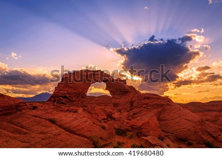 Desert sunset with a natural arch, Utah, USA. - stock photo