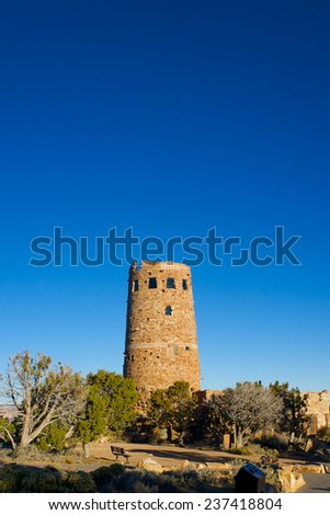 Desert Watchtower glows in the morning sun on the edge of the Grand Canyon. - stock photo