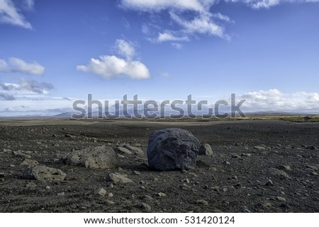 Desert wilderness in the Icelandic highlands, sand and rocks in the foreground and mountains in the distance