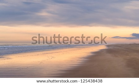 Deserted beach at sunset - stock photo
