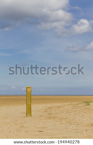 Deserted Beach with solitary wooden post on a beautiful sunny day - stock photo