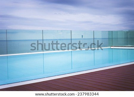 Deserted cool blue inviting swimming pool on a paved patio overlooking the ocean surrounded by a wire mesh fence, , idyllic summer background - stock photo