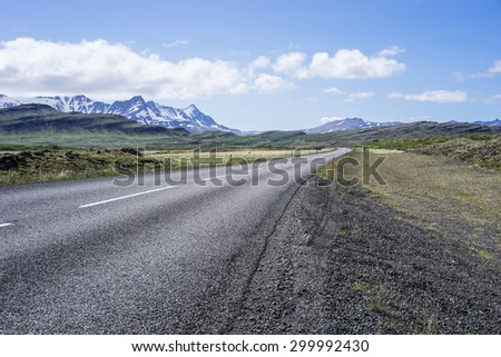 Deserted Icelandic tarmaced road curving into the distance - stock photo