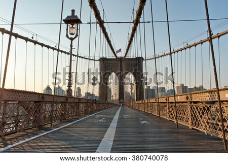 Deserted Pedestrian Walkway Through Arches and Support Cables of Historic Brooklyn Bridge, an Iconic Tourist Destination and Landmark in New York City, New York, USA at Sunset