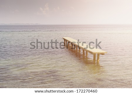 Deserted rustic wooden jetty surrounded by water at high tide or flooding in a calm tranquil ocean with copyspace - stock photo