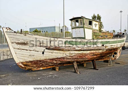 Deserted rusty old and broken wooden boat on the coast of a ocean Costa de la Luz in port Spain