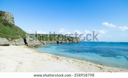 Deserted tropical beach cove with clear blue water and coral rock coastline, Okinawa, Japan - stock photo
