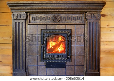 Design Burning fireplace with cast iron door near the wooden wall. - stock photo