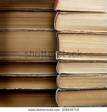 Design concept of wisdom and knowledge power - close up view on stacked old books placed on grunge paper background with place for your text or figure