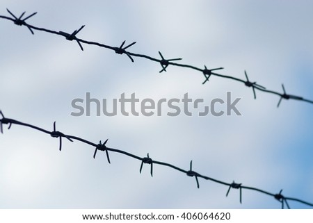 design from a barbed wire against the cloudy sky for a protection of prison or for other prohibited zone