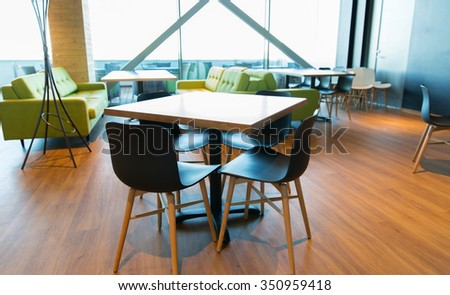 design, public place, furniture and interior concept - close up of restaurant interior with table and chairs - stock photo
