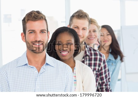 Design team standing in a line smiling at camera in creative office - stock photo