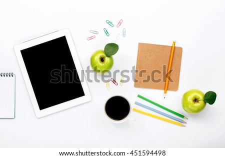 Design workspace. tablet, notebook, colored pencils, paper clips, green apple and cup of black coffee on a white background. top view, flat lay - stock photo