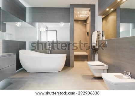 Designed freestanding bath in gray modern bathroom - stock photo