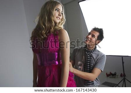 Designer adjusting fashion model's dress in studio - stock photo