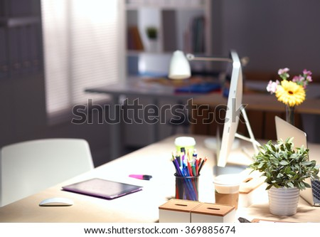 Designer desk with laptop in the office - stock photo