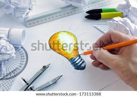 Designer drawing a light bulb, concept for brainstorming and inspiration - stock photo