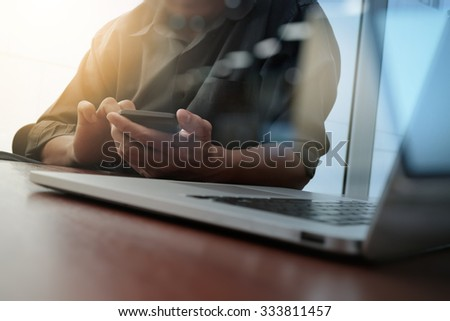 designer hand working and smart phone and laptop on wooden desk in office as concept