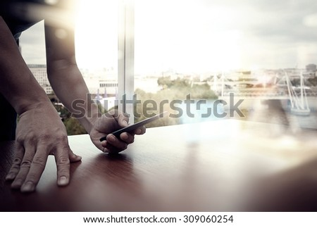 designer hand working and smart phone and laptop on wooden desk in office with london city background  - stock photo
