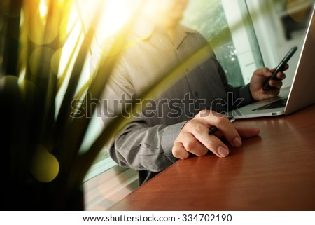 designer hand working laptop with green plant foreground on wooden desk in office - stock photo